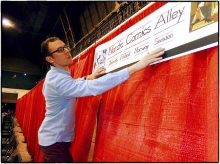 Seriefrämjandets verksamhetsledare Jamil Mani sätter upp den speciellt framtagna vepan för Nordic Comics Alley.