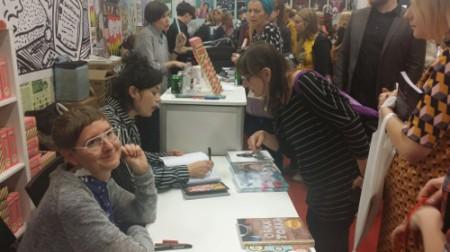 Liv Strömqvist signerar en bok åt Vicky Uhlander. I förgrunden syns Lotta Sjöberg.