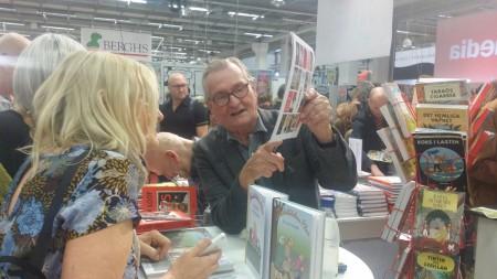 """Sven-Bertil Bärnarp signerar en almanacka med """"Medelålders Plus"""" åt Ulla Eriksson på Bokmässan 2015. Foto: Malinda Lindmark."""