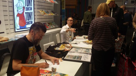 Jonas Darnell (t.v.) och Tony Cronstam (t.h.) signerar i Egmonts monter på Bokmässan 2015. Foto: Malinda Lindmark.